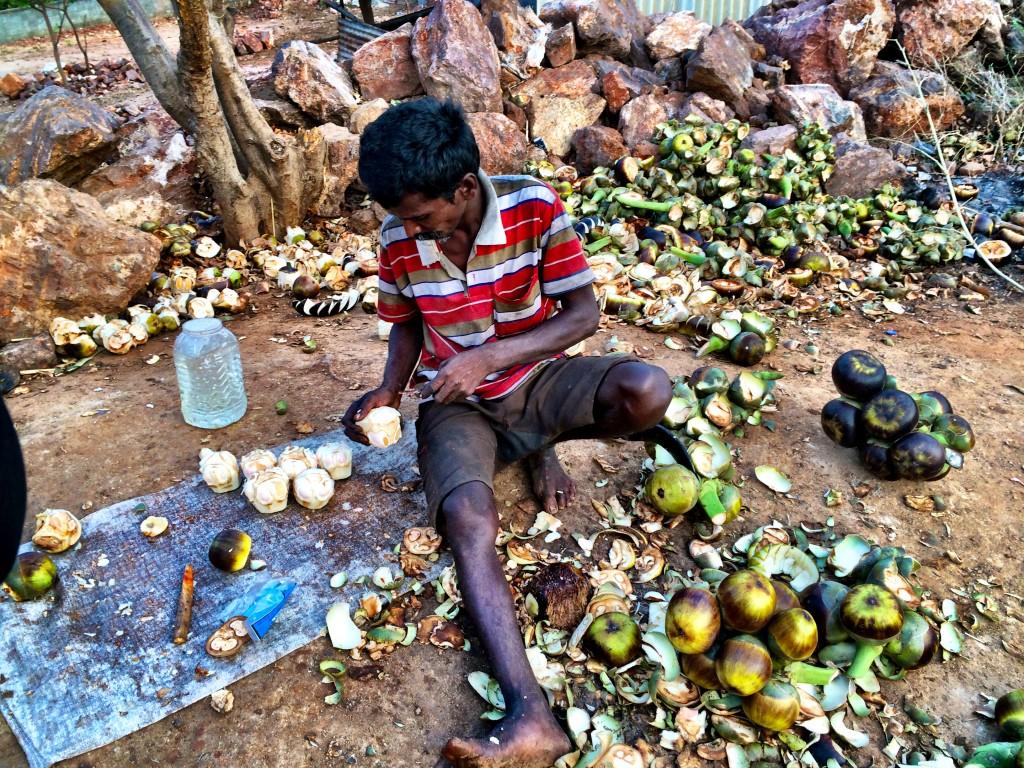 A palm fruit vendor preparing the fruit alongside the road
